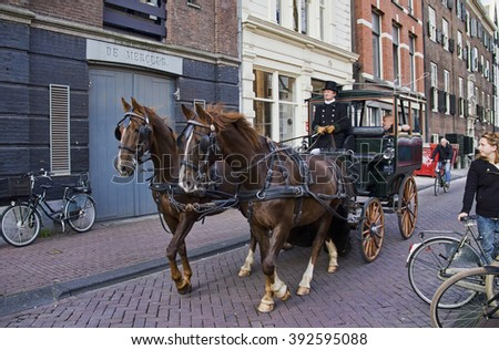 Amsterdam, Holland - November 12, 2015: Horse and wagon carrying tourists in a street in old Amsterdam on November 12, 2015 in Amsterdam, Holland.