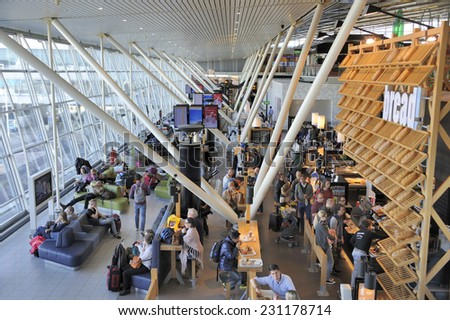 AMSTERDAM,HOLLAND-NOVEMBER 1, 2014; People relaxing, waiting and eating at the departure hall of Schiphol airport. November 1, 2014 Amsterdam - stock photo