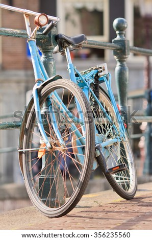 AMSTERDAM-JULY 20, 2009. Blue vintage bicycle parked against a railing. With 881,000 the city has more bicycles than residents. 58% of the residents use its bicycle daily for shopping and commuting. - stock photo