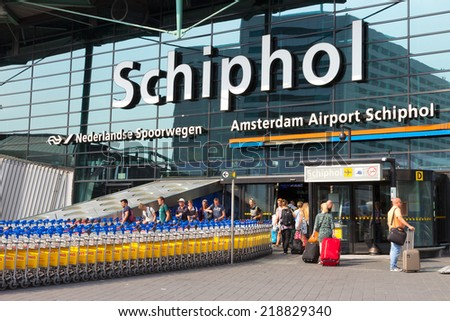 AMSTERDAM - JULY 31: Main entrance to Schiphol Airport on July 31, 2014 in Amsterdam, Netherlands. The airport handles over 45 million passengers per year with almost 100 airlines flying from here.  - stock photo