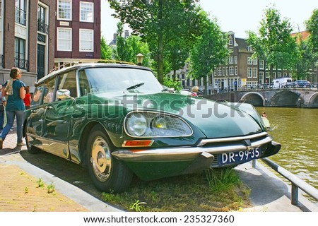 AMSTERDAM - JULY 01, 2010: Retro car Citroen DS parked on the embankment of the canal, on July 01 in Amsterdam.
