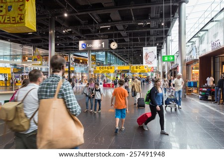 AMSTERDAM - 19 JULY, 2014: Travellers shopping in Schiphol Airport. - stock photo