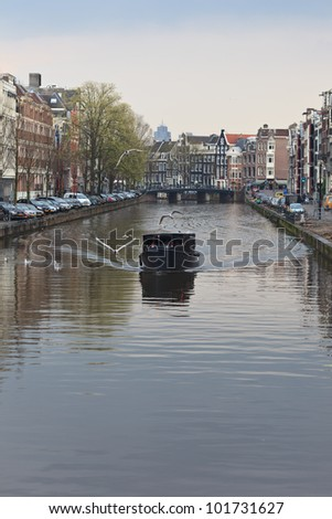 AMSTERDAM, NETHERLANDS - APR 20: Tourist boat cruises on canal in Amsterdam on April 20, 2012. Almost 20 percent of all canal cruise boats are now electrically powered