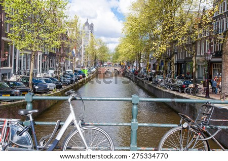 AMSTERDAM,NETHERLANDS-APRIL 27: Amsterdam canal with bikes on the bridge and parked cars along the bank on April 27, 2015 in Amsterdam, Netherlands. - stock photo