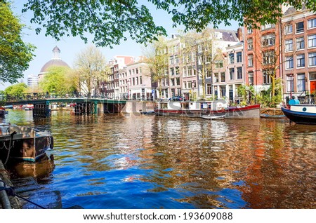 Amsterdam, Netherlands.-APRIL 23: Amsterdam canals on April 23, 2014. Beautiful view of Amsterdam canals and typical dutch houses. - stock photo