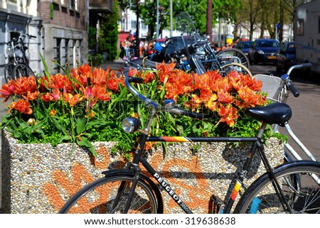 Amsterdam, Netherlands - April 30, 2012: Bike with flowers. Bicycle is parked near flower pots on a background of city streets and parking lots.