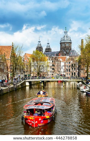 AMSTERDAM, NETHERLANDS - APRIL 9: Boat tour of Amsterdam city with Saint Nicholas church in the background along with canal on April 9, 2016. - stock photo