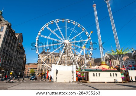 AMSTERDAM,NETHERLANDS-APRIL 27: Ferris wheel on Dam Square on the eve of King's Day on April 27,2015 in Amsterdam.  King's Day is the largest open-air festivity in Amsterdam.
