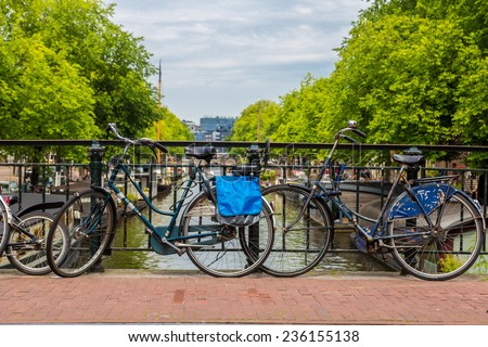 AMSTERDAM, NETHERLANDS - AUGUST 19: Bicycles on a bridge over the canals of Amsterdam. Amsterdam is the capital and most populous city of the Netherlands on August 19, 2014
