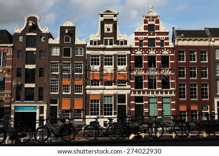 AMSTERDAM, NETHERLANDS - AUGUST 9, 2012: Bicycles parked in front of the traditional Dutch brick houses on Rokin Street in Amsterdam, Netherlands. - stock photo