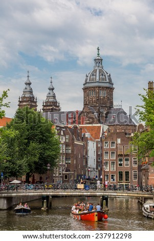 AMSTERDAM, NETHERLANDS - AUGUST 19: Canal and St. Nicolas Church in Amsterdam. Amsterdam is the capital and most populous city of the Netherlands on August 19, 2014