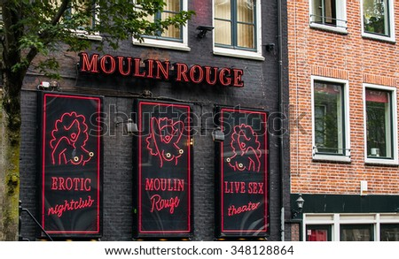 AMSTERDAM, NETHERLANDS - AUGUST 22: club Moulin Rouge in the red light district on August 22, 2015 in Amsterdam. The district is world reknown and famous attraction for tourists. - stock photo