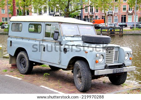 AMSTERDAM, NETHERLANDS - AUGUST 10, 2014: Cyan retro car Land Rover Series III at the city street. - stock photo