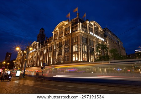 AMSTERDAM, NETHERLANDS - AUGUST 21, 2012: Illuminated De Bijenkorf store on Dam Square. De Bijenkorf is a chain of high-end department stores in the Netherlands. - stock photo