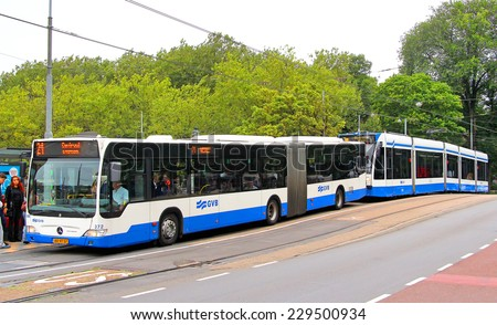 AMSTERDAM, NETHERLANDS - AUGUST 10, 2014: Modern articulated bus Mercedes-Benz O530 Citaro G and the tramway Siemens Combino at the city street. - stock photo