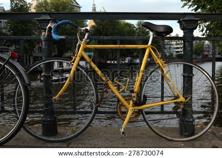 AMSTERDAM, NETHERLANDS - AUGUST 9, 2012: Old yellow bicycle parked on the bridge over a gracht in Amsterdam, Netherlands.  - stock photo