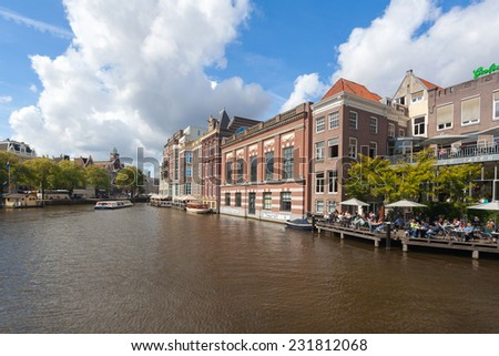 AMSTERDAM - NETHERLANDS: AUGUST 14, 2014: People sitting at the cafe on dock next to NH Doelen Hotel.