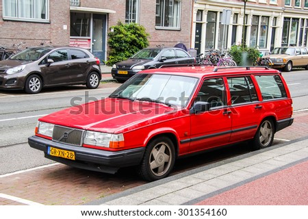 AMSTERDAM, NETHERLANDS - AUGUST 10, 2014: Red retro estate car Volvo 940 at the city street. - stock photo