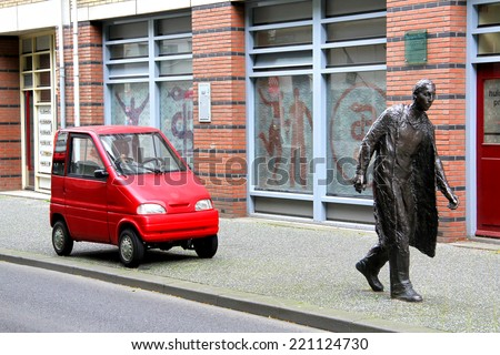 AMSTERDAM, NETHERLANDS - AUGUST 10, 2014: Tiny car Canta LX at the city street near the statue of a pedestrian. - stock photo