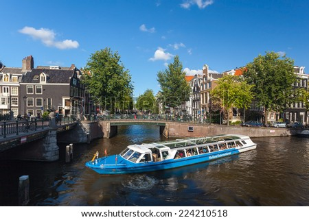 AMSTERDAM - NETHERLANDS: AUGUST 1, 2014: Tourist city sightseeing boat in the canal. - stock photo