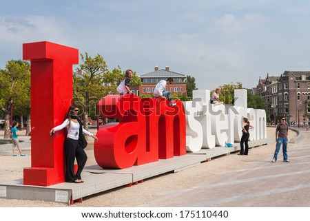 "AMSTERDAM, NETHERLANDS - AUGUST 2, 2007: Tourists posing on popular ""I Amsterdam"" slogan in front of the Rijksmuseum. Tourists photograph themselves, in, around and on top of the slogan. - stock photo"