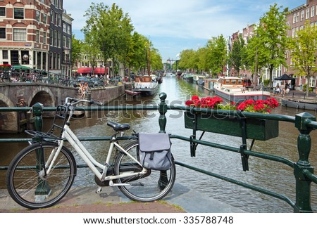 AMSTERDAM, NETHERLANDS - AUGUST 20, 2012: White bicycle parked on a bridge overlooking canals in Amsterdam, which is the world most watery city with more than one hundred kilometers of canals. - stock photo