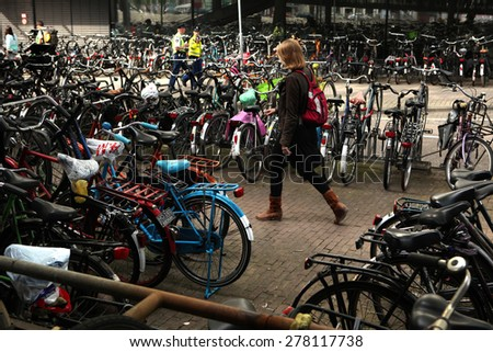 AMSTERDAM, NETHERLANDS - AUGUST 9, 2012: Woman walks through the bicycle parking station next to the Central railway station in Amsterdam, Netherlands. - stock photo