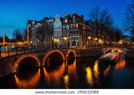 Amsterdam, Netherlands canals and bridges. Night view of Keizersgracht and famous touristic place with boat and water reflection - stock photo
