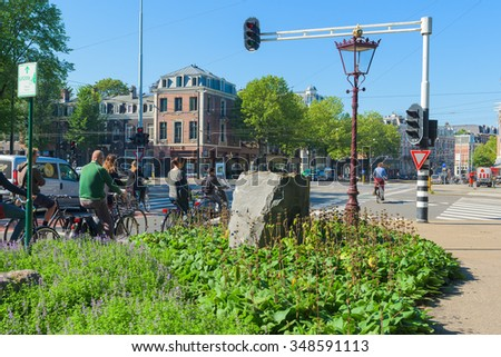AMSTERDAM, NETHERLANDS - CIRCA SEPTEMBER 2015: People at the city center streets ride on bicycles.
