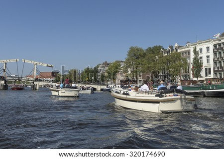 AMSTERDAM, NETHERLANDS - CIRCA SEPTEMBER 2015: Tourist at boat excursion over canals