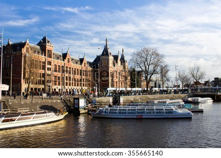 Amsterdam,Netherlands â?? December 23, 2015 : Amsterdam sightseeing boat tour with Amsterdam central in blackground - stock photo