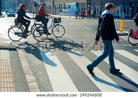 AMSTERDAM, NETHERLANDS - FEB 26, 2014: Unidentified people  crossing the street. It is one of the most cycle-friendly cities in the world. 58% of the citizens uses daily a bicycle.  - stock photo