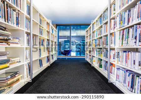 AMSTERDAM, NETHERLANDS â?? February 8, 2015: light-modern library with bookshelves and white LED light - stock photo