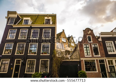 AMSTERDAM, NETHERLANDS - JANUARY 10, 2017: Famous vintage buildings of Amsterdam city at sun set. General landscape view at tradition Dutch arcitecture. January 10, 2017 - Amsterdam - Netherlands.