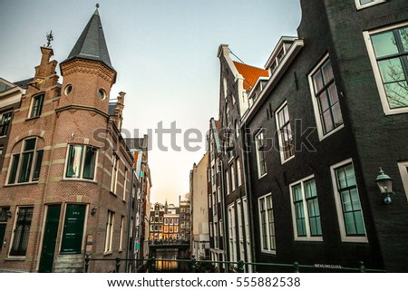 AMSTERDAM, NETHERLANDS - JANUARY 09, 2017: Famous vintage buildings of Amsterdam city at sun set. General landscape view at tradition Dutch architecture. January 09, 2017 - Amsterdam - Netherlands.