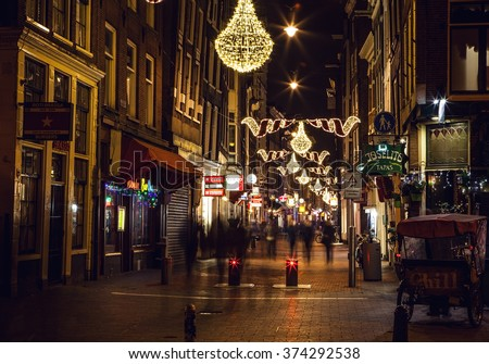 AMSTERDAM, NETHERLANDS - JANUARY 20, 2016: Night streets of Amsterdam with blurred silhouettes of passersby on January 20, 2016 in Amsterdam - Netherland.