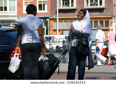 AMSTERDAM, NETHERLANDS - JUL 4, 2009: Two smiling African black women speaking on the street. Amsterdam is one of the most multicultural capitals Europe, is home to 200 different nationalities - stock photo