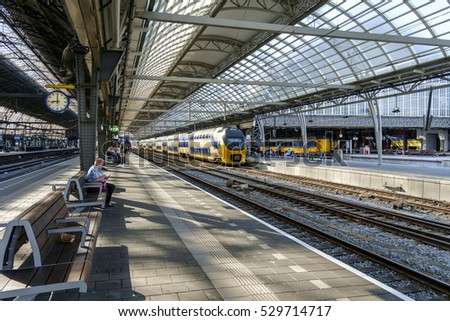 Amsterdam, Netherlands, Juli 2016: Overview of the platforms in Amsterdam Centraal Station railway station on a quiet moment, with a few trains and passengers waiting