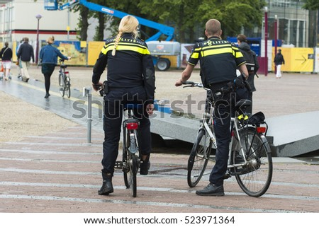 AMSTERDAM, NETHERLANDS - JULY 8, 2015: A couple of cops, mounted on bicycles patrol the streets of the city.