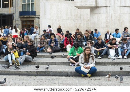 AMSTERDAM, NETHERLANDS - JULY 8, 2015: A large group of people sitting on a staircase, in a central square of the city.