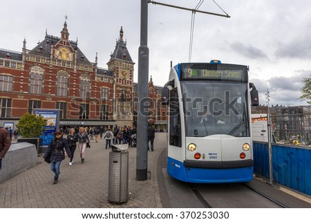 AMSTERDAM, NETHERLANDS - JULY 29, 2015: A tram traveling in front of Station Amsterdam Centraal. It is the largest railway station of Amsterdam, Netherlands, and a major national railway hub. - stock photo