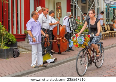 Amsterdam, Netherlands - July 29,2014: A typical Amsterdam street with cyclist and street musicians (Buskers) near cafes.  In Amsterdam, there are about 600,000 bikes. Focus on cyclists. - stock photo