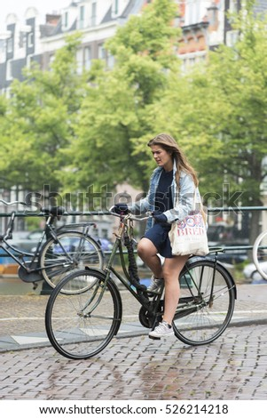 AMSTERDAM, NETHERLANDS - JULY 8, 2015: A woman riding a bike, stroll through one of the streets of the city, in the rain.