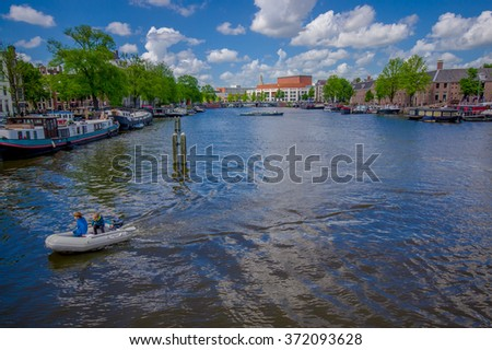 Amsterdam, Netherlands - July 10, 2015: Large water channel running through city with several boats parked alongside, green trees sourrounding and beautiful blue sky - stock photo