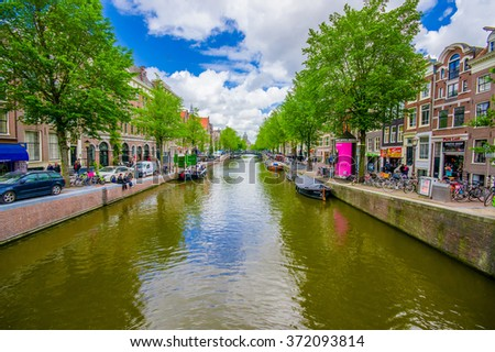 Amsterdam, Netherlands - July 10, 2015: One of many water channels running through the city, small boats parked alongside pier - stock photo