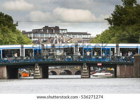 AMSTERDAM, NETHERLANDS - JULY 8, 2015: People crossing a bridge over one of the canals, where bikes are parked, a long tram the background.