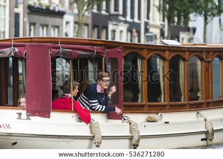 AMSTERDAM, NETHERLANDS - JULY 8, 2015: Some teenagers, passengers on a boat trips along the canals of the city.
