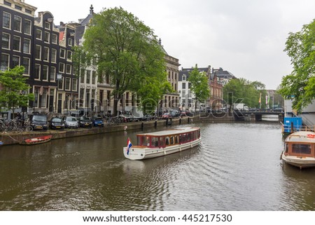 AMSTERDAM, NETHERLANDS - JUNE 23, 2016: A sightseeing tour boat in a canal in amsterdam, Netherlands. Amsterdam Canal Cruises are one of the best ways to enjoy the city in a short time. - stock photo