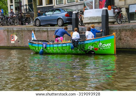 Amsterdam, Netherlands - June 20, 2015: Children in boat publicizing ecological way of life on the canal in Amsterdam. - stock photo