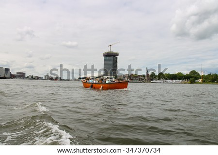 Amsterdam, Netherlands - June 20, 2015: People in the boat on tours of the canals of Amsterdam - stock photo